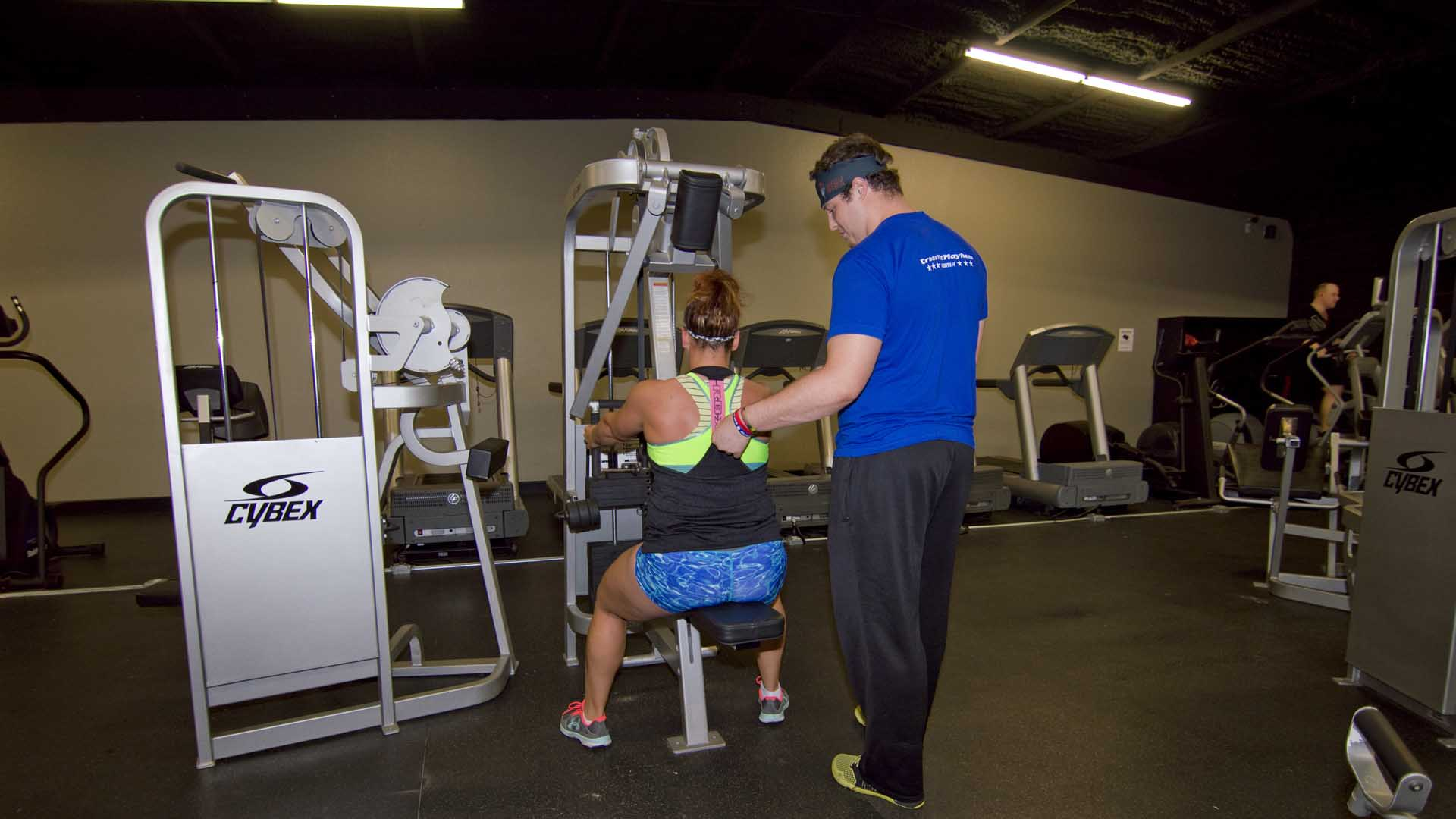 Cody instructing a client to squeeze her shoulder blades at the end of an exercise.