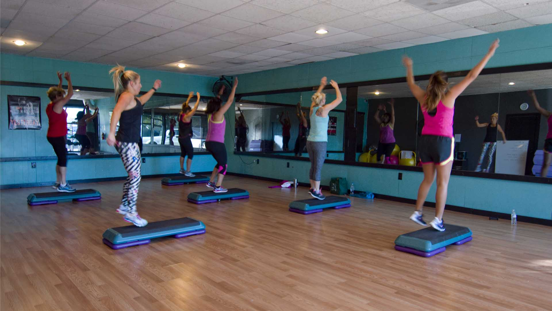 A group of women participating in Kathy's group fitness class, jumping up off their aerobics steps and raising their hands in the air.