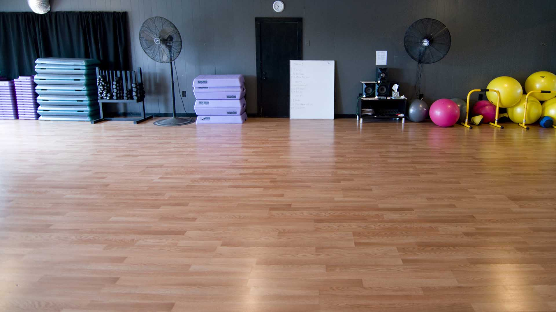 Aerobics steps, fitness balls and a dumbbell rack stand against the wall at the back of the Group Fitness room at Revival Fitness in Gonzales, TX.