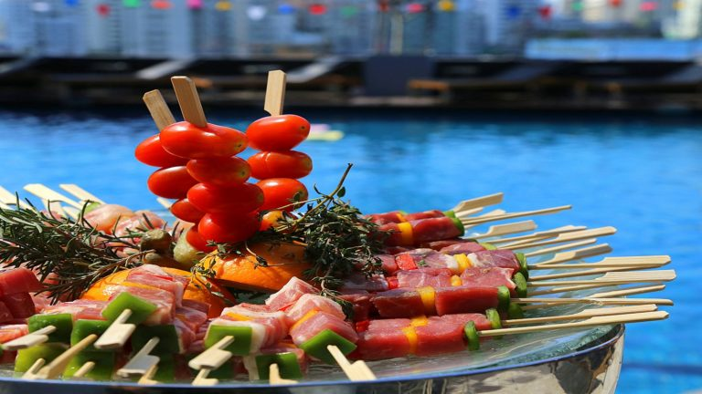 fun party food on a table near the pool