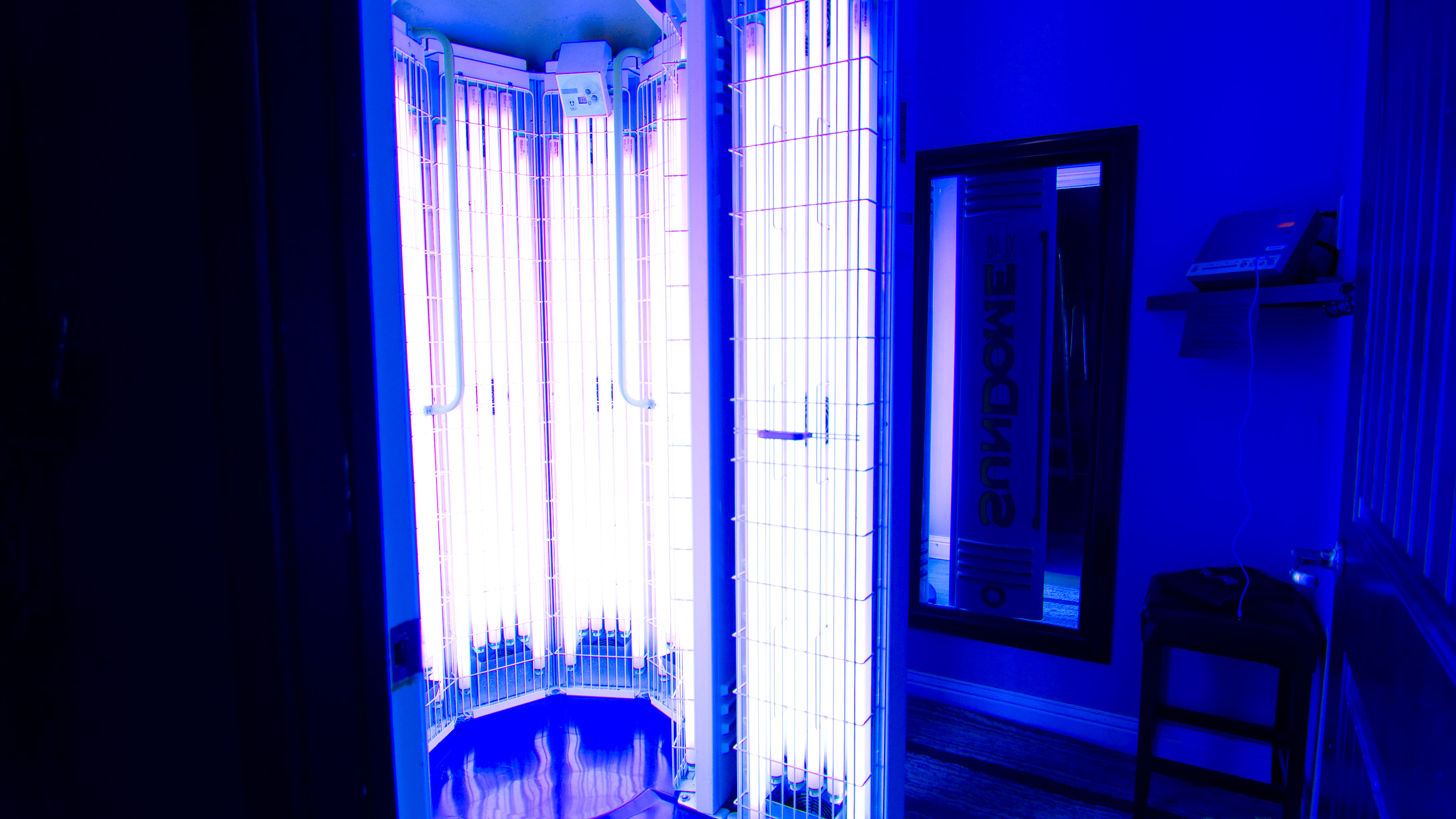 View of tanning room number 1 with our stand up tanning booth having doors open and bulbs on.