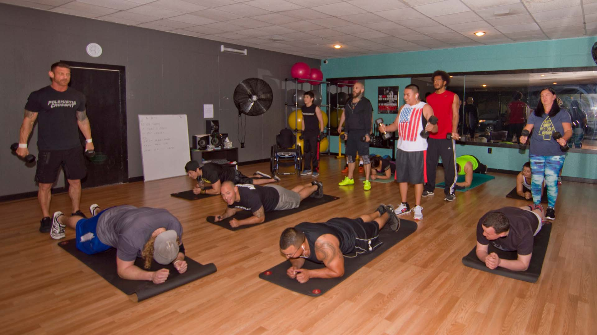 Some people lay in the prone position on the floor, while others perform a standing bicep curl at Cody's Boot Camp Class