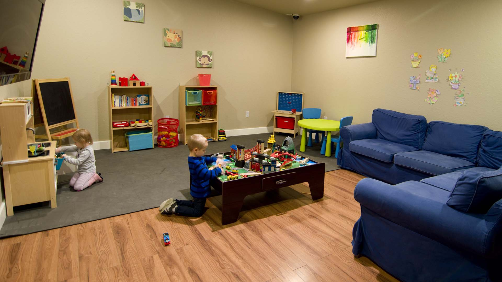 A little boy plays with a toy train set, while a little girl has fun with the play kitchen in Kids Club.