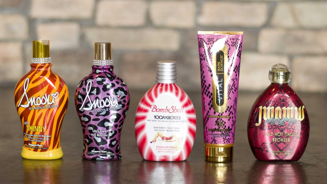 A lineup of high quality Tingle Tanning Lotions with a stone wall in the background.