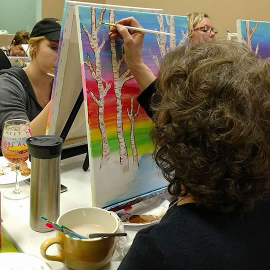 Women painting during a canvas class.