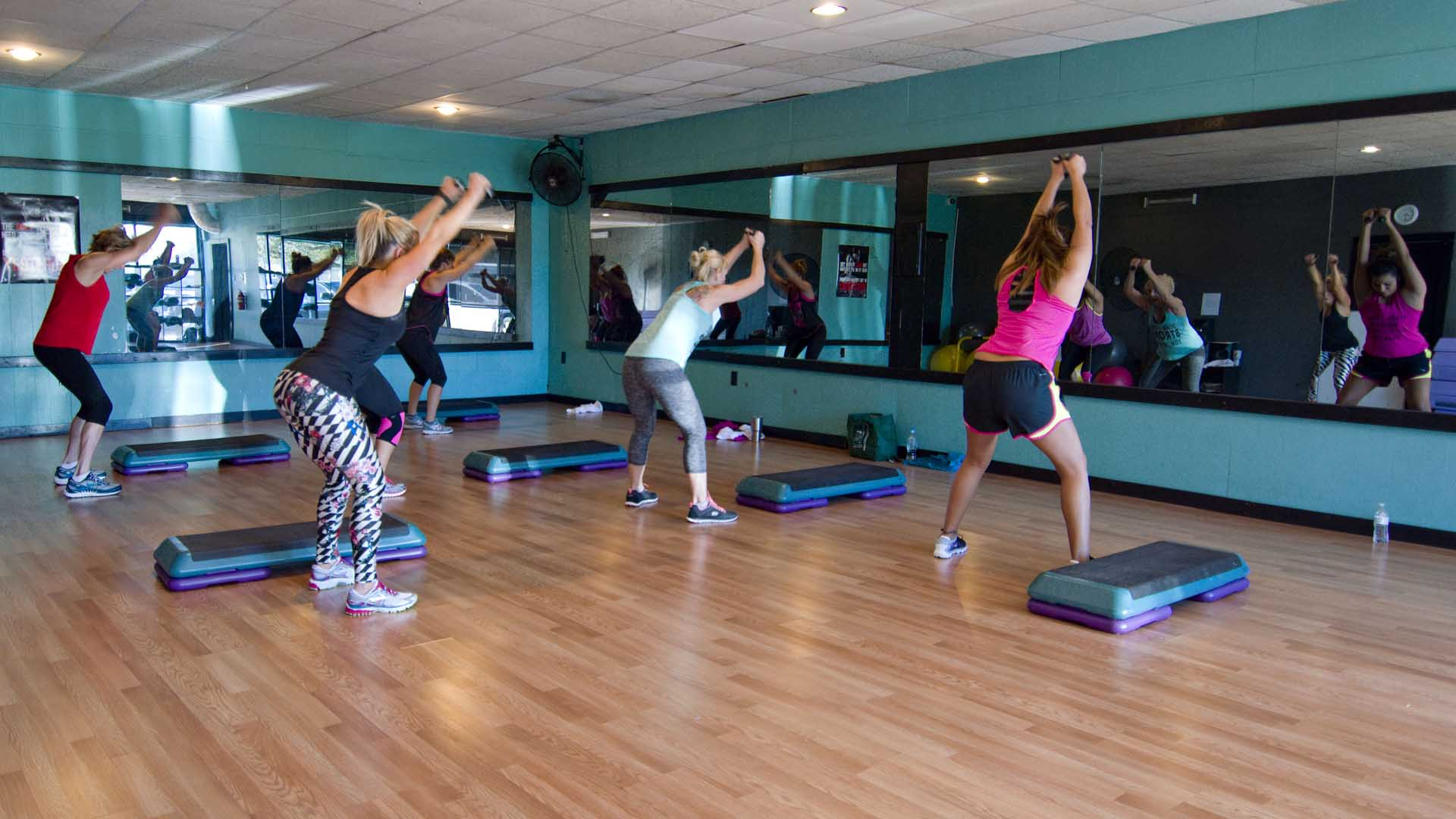 A group of women participating in Kathy's group fitness class standing next to their aerobics steps with feet shoulder width and hands in the air.