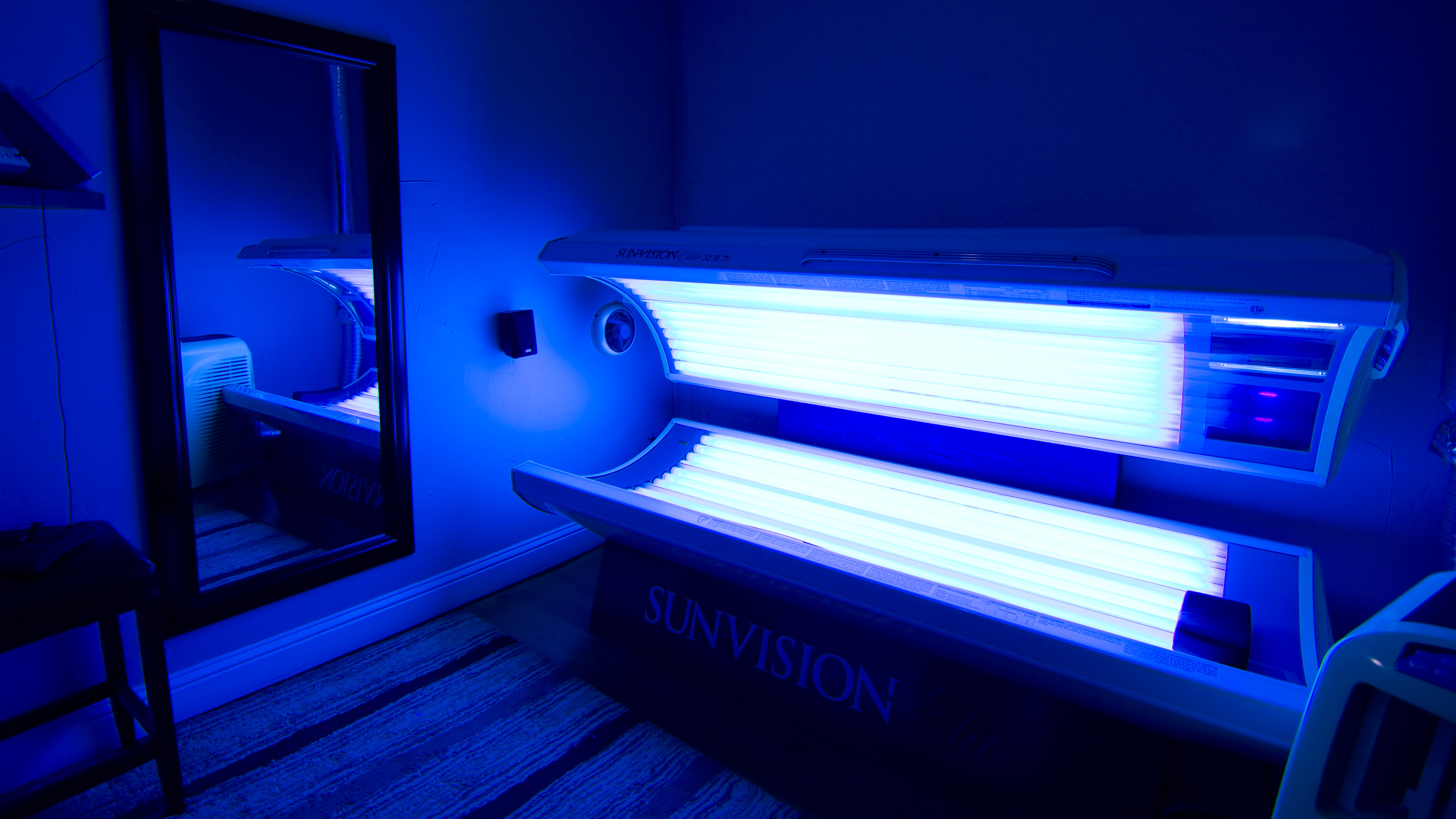 View of tanning room number 2, with our lay down tanning bed in the open position and bulbs on.