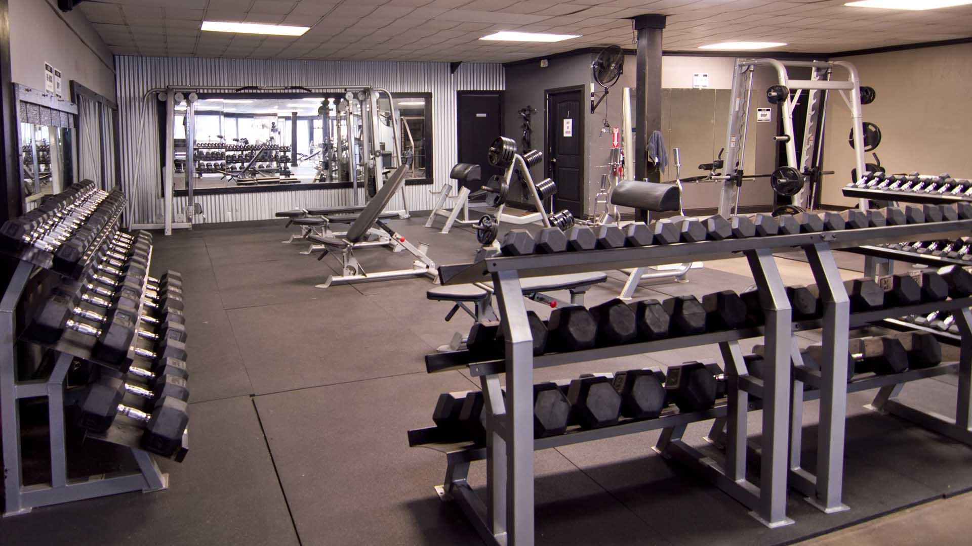 Three racks of dumbbells form a U shape and enclose the free weight section of the gym.