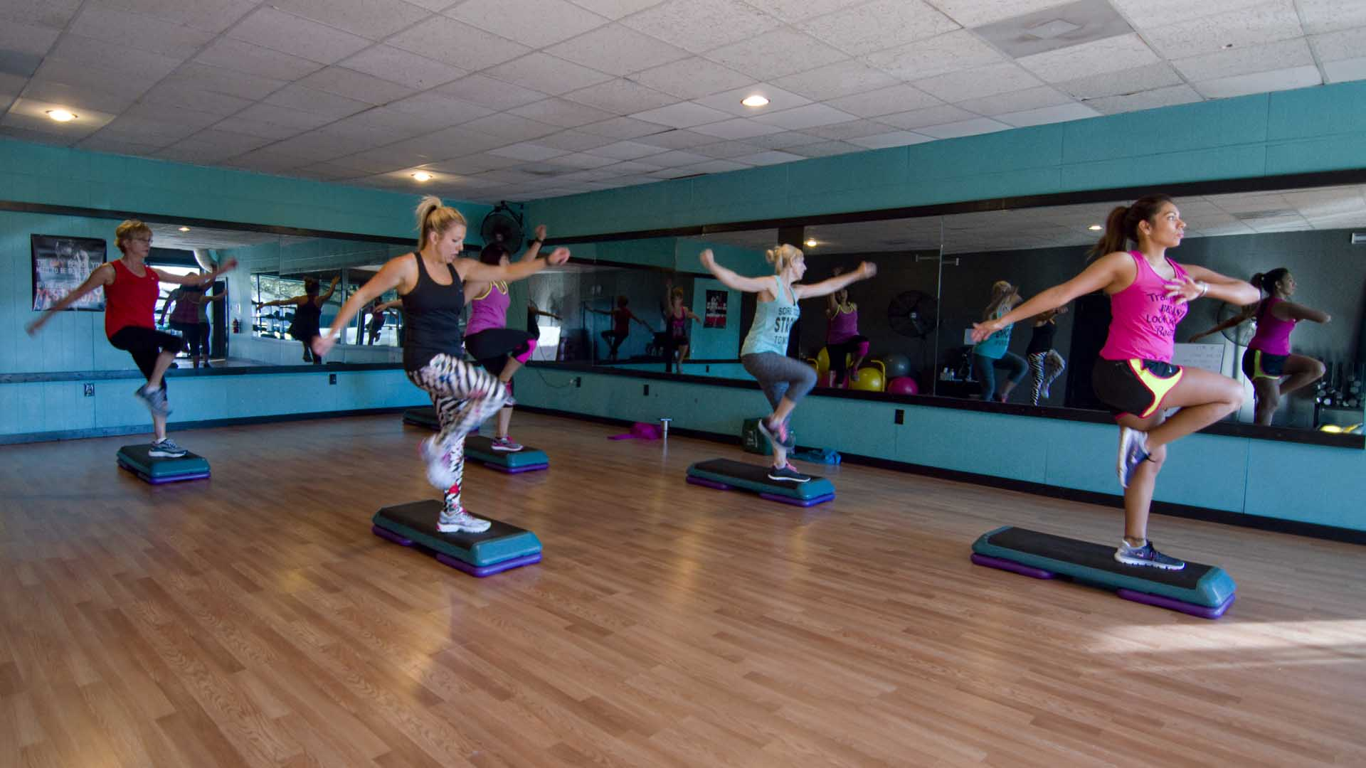 A group of women participating in Kathy's group fitness class, standing on one foot atop their aerobics steps while lifting the other leg with knee forward and arms lifted up to the side.