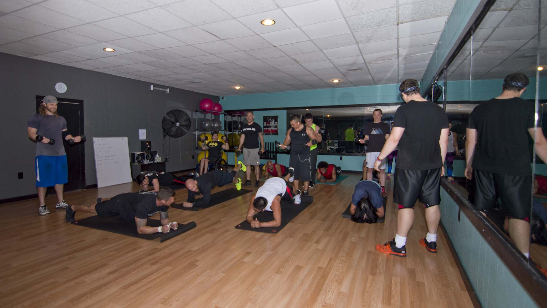 Cody instructs one group of students to lift a leg from the prone position, while other students perform a standing dumbbell bicep curl.