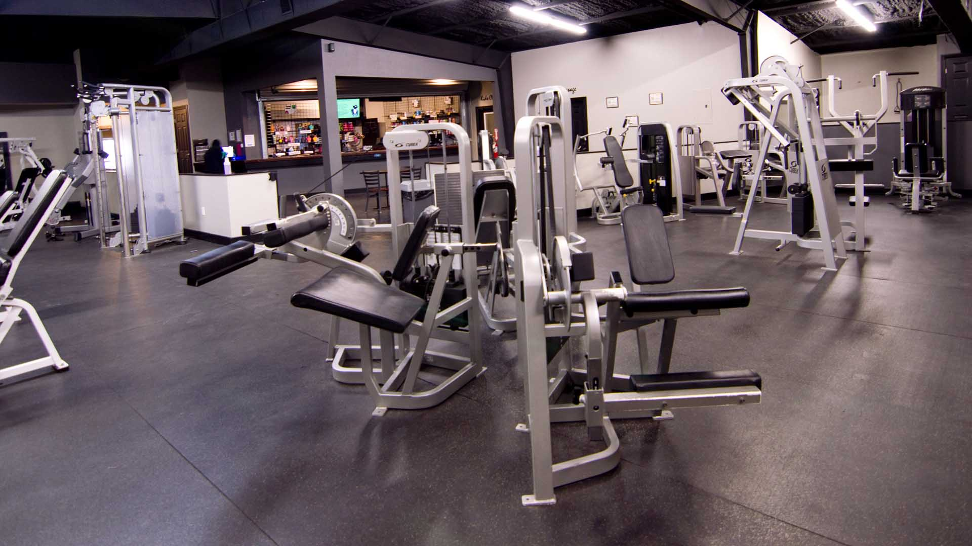 Three pieces of Cybex gym equipment stand back to back in a triangular setup.