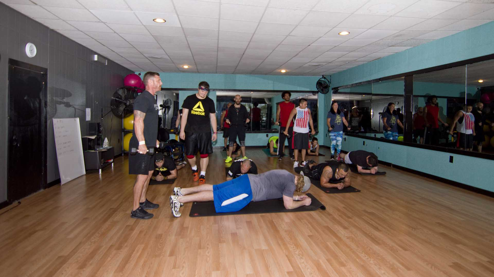 Cody checks the form of a man performing a core exercise at the Boot Camp Group Fitness class.