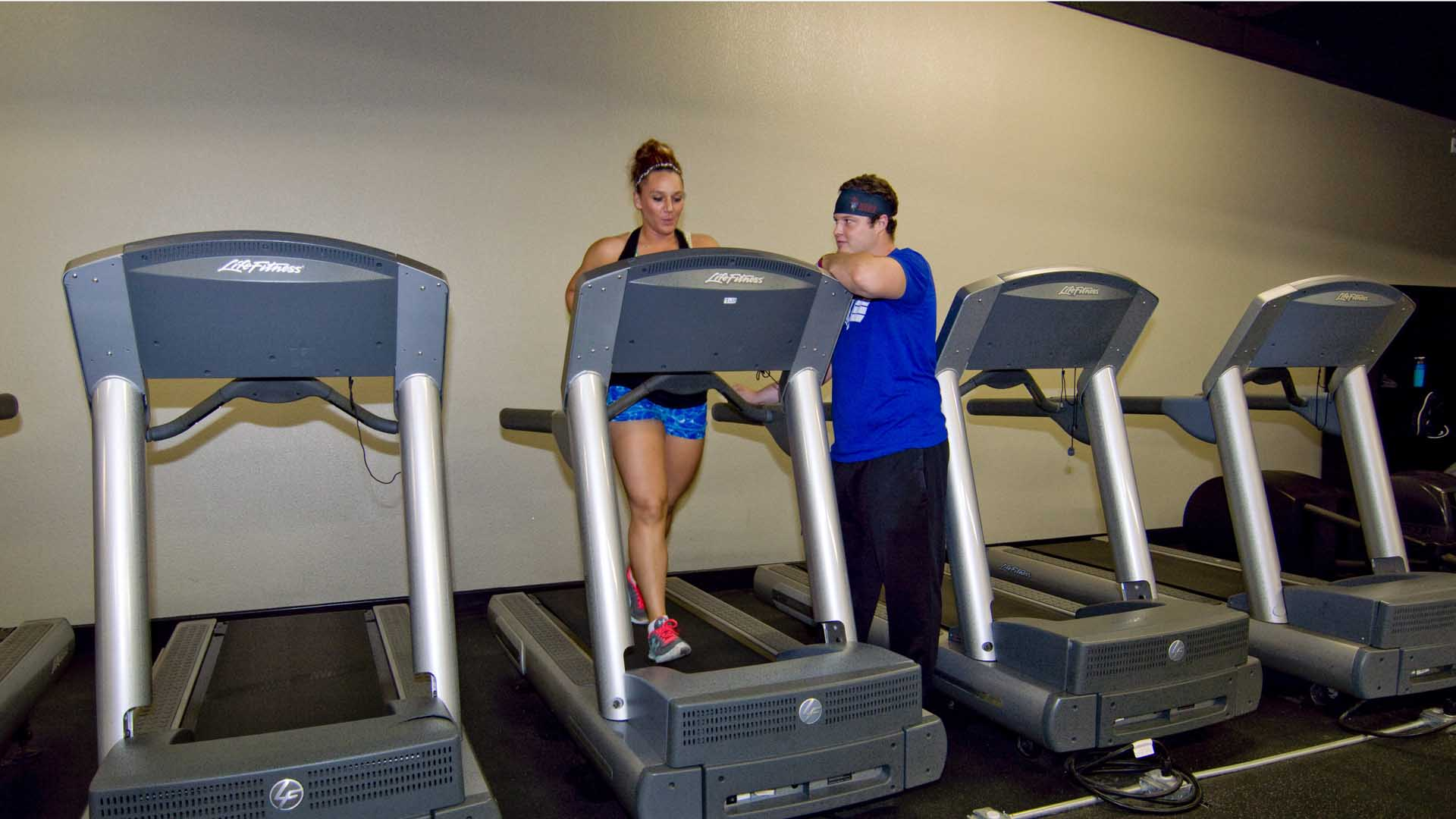 Cody standing with a personal training client walking on a treadmill.