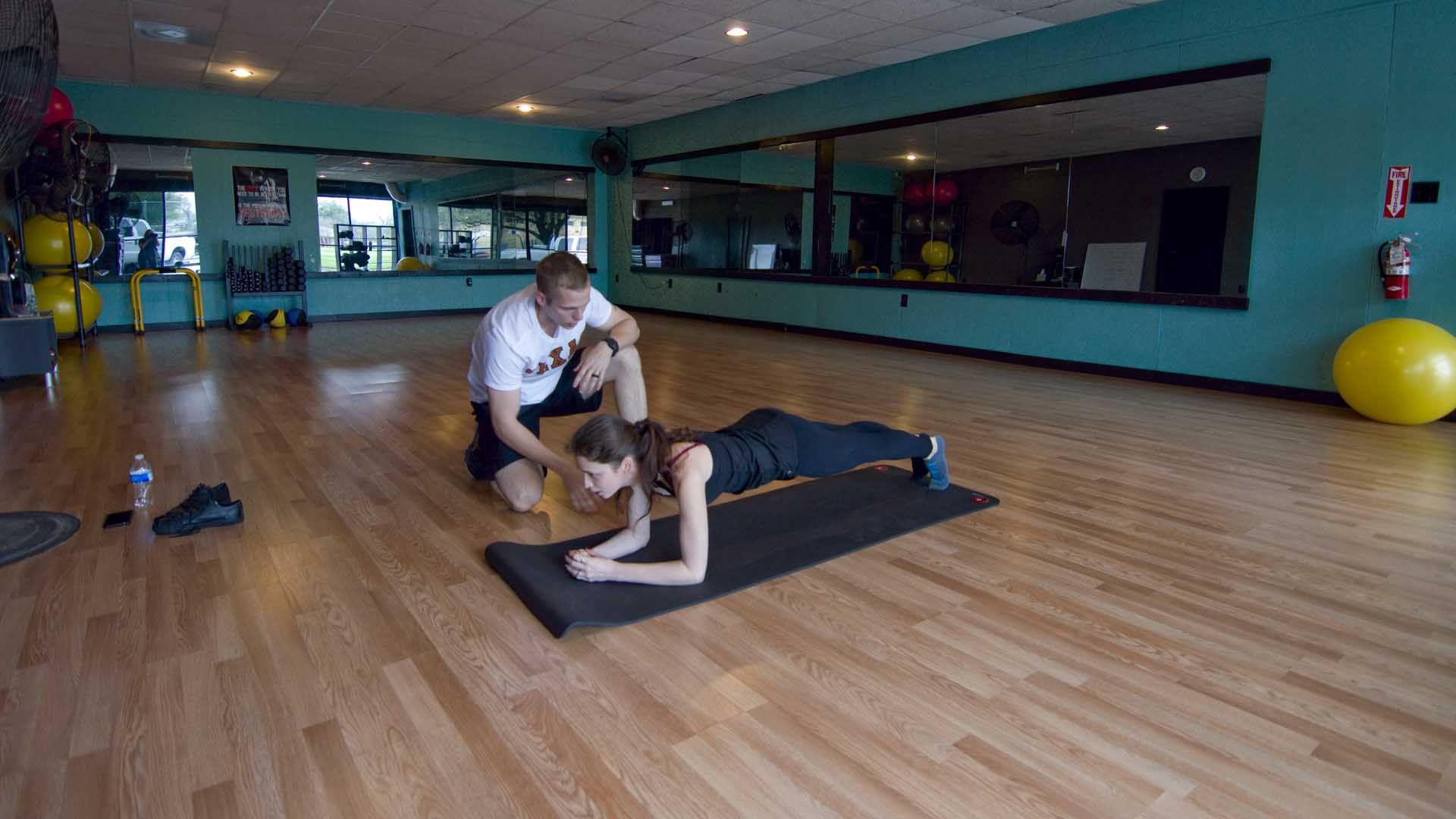 CJ doing a core exercise with a client.