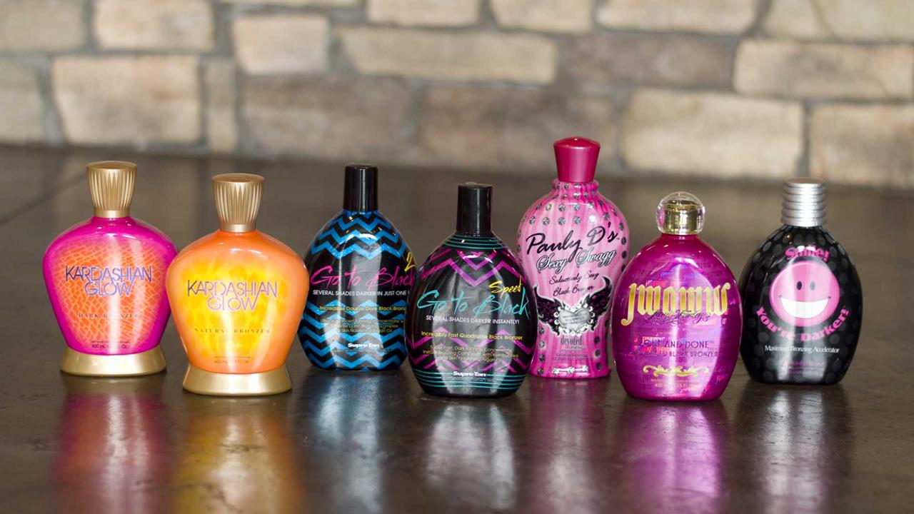 A lineup of high quality Bronzer Tanning Lotions with a stone wall in the background.