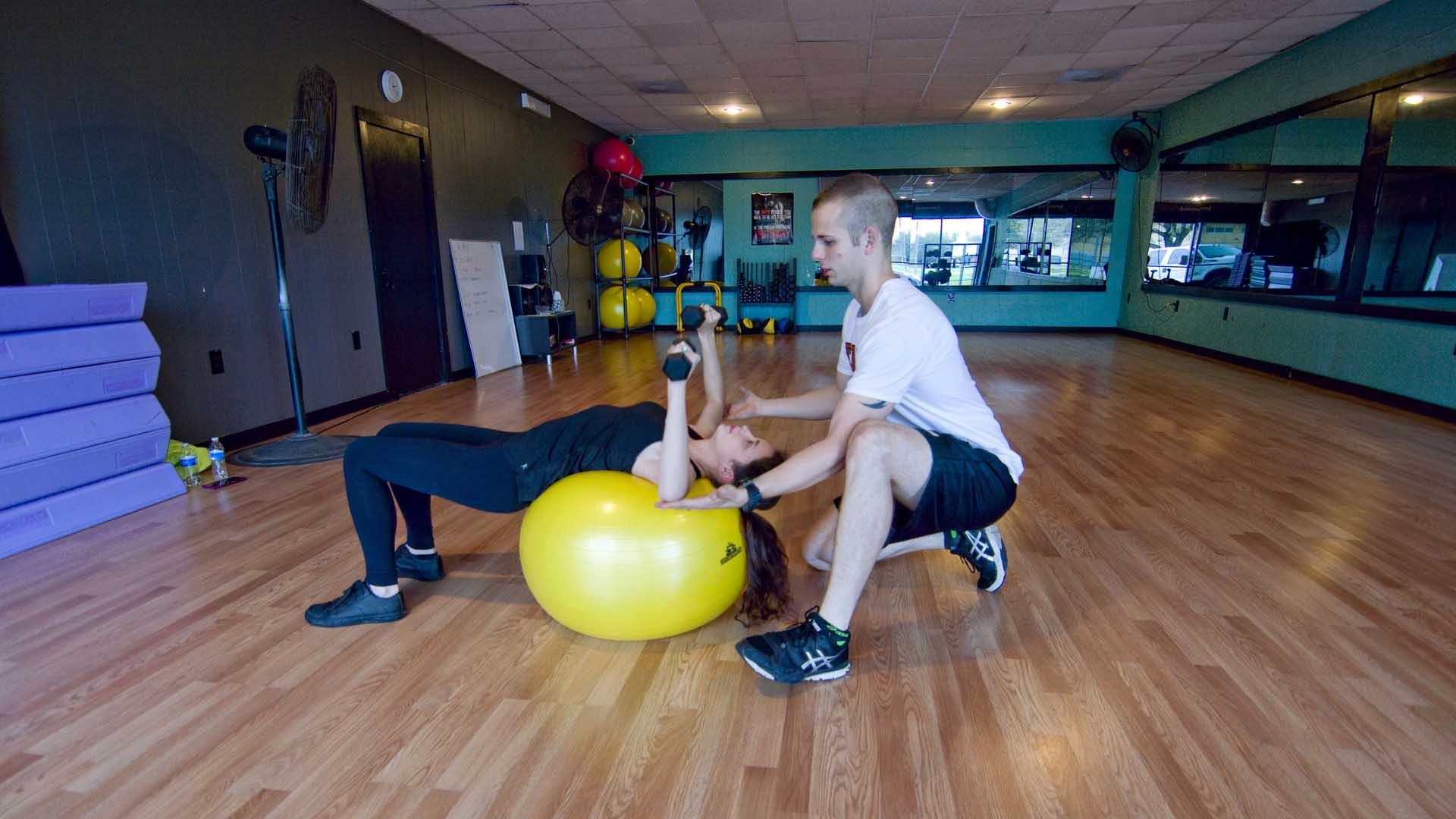 Personal Trainer CJ holds his hands under a clients elbows to show her the end of the range of motion on a dumbbell chest press on an exercise ball.