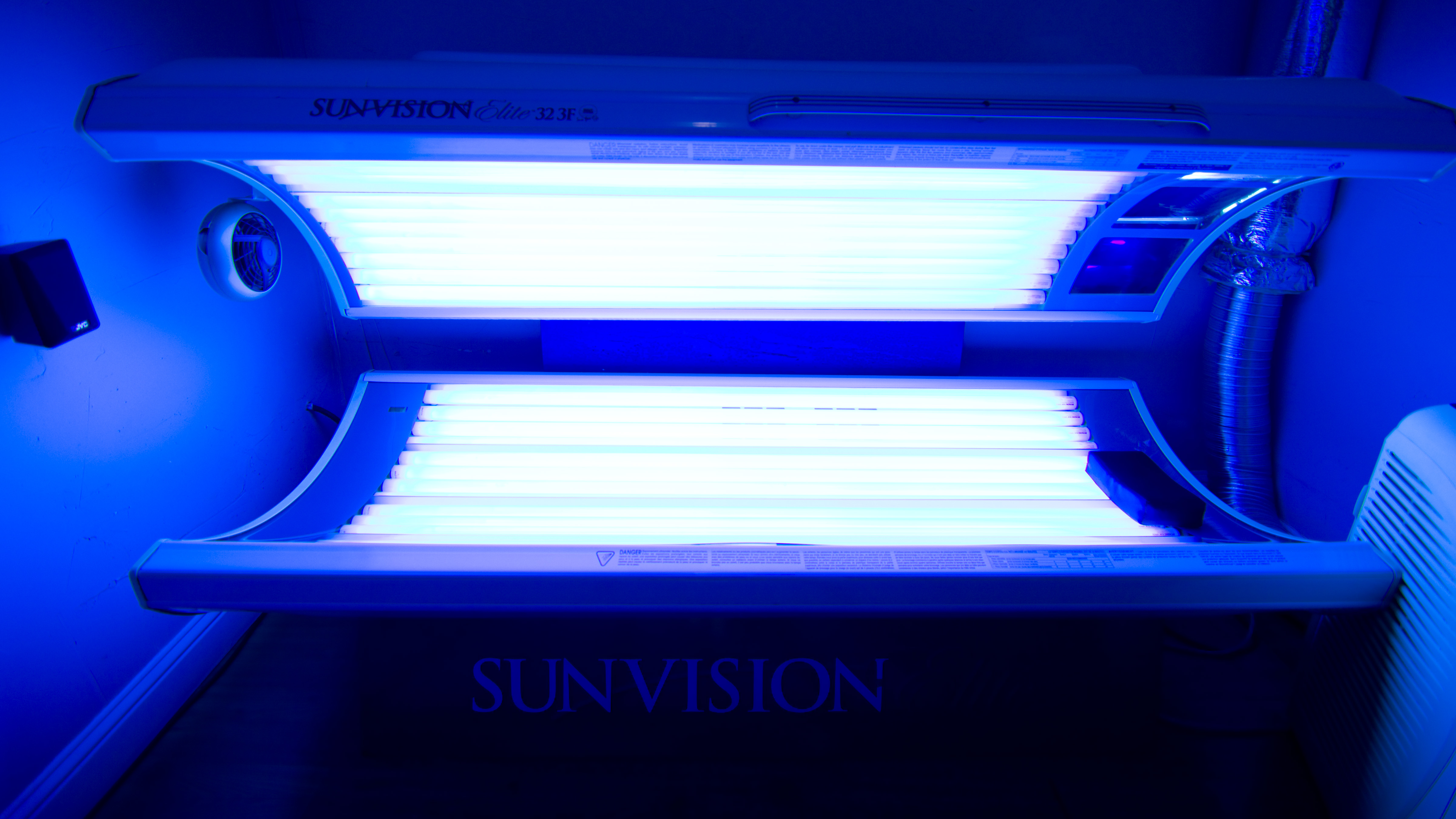 Closeup of our lay down tanning bed, in the open position with bulbs on.